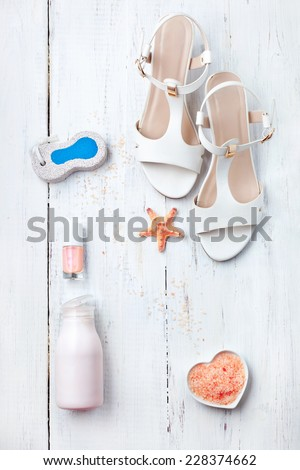 Set of summer women's accessories - sandals, bath salt, pumice stone, body cream and nail polish, on wooden floor. White collection. - stock photo