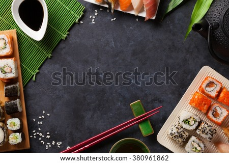 Set of sushi and maki roll and green tea over stone table. Top view with copy space - stock photo