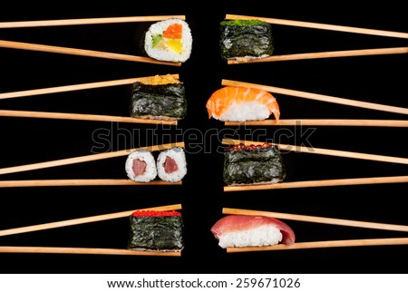 Set of sushi pieces in chopsticks, isolated on black background - stock photo