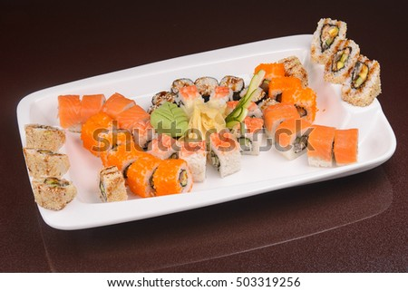 set of sushi rolls on a white plate,  japanese food, glass dark background