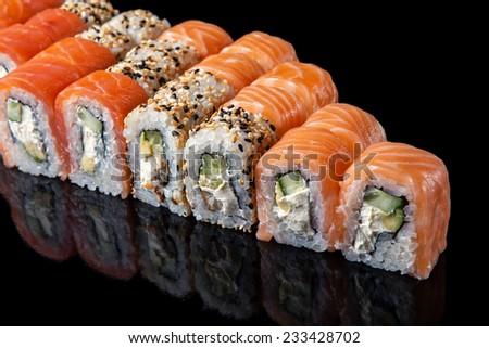 set of sushi rolls on black background - stock photo