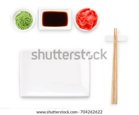 Set of sushi tablewear. Top view on empty rectangular sushi plate with hieroglyphs, saucer, ginger, wasabi and chopsticks at white background. Flat lay, copy space
