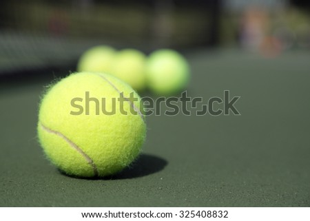 Set of tennis balls on a green tennis court - stock photo
