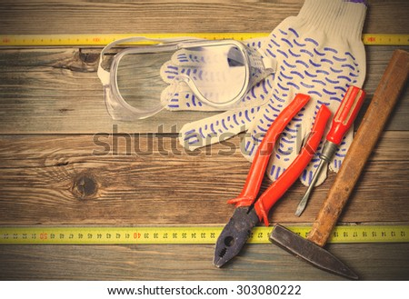 set of the old locksmith tools, safety glasses and work gloves on the vintage workbench. instagram image filter retro style - stock photo