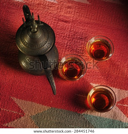 Set of three arabic coffee cups and old coffee pot. View from top. - stock photo