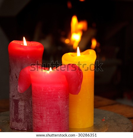 Set of three burning candles in front of a burning fire place - stock photo