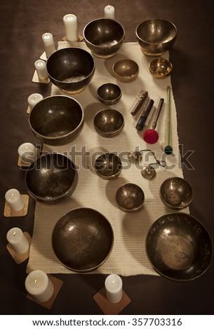 Set of Tibetan singing bowls with burning candles - stock photo