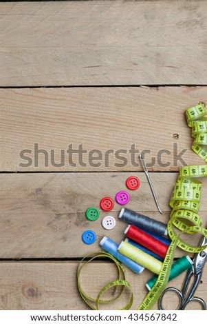 Set of tools with buttons, needle, thread spools for home made embroidery, needlework and tailoring, on wooden background. - stock photo