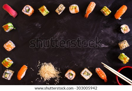 Set of traditional japanese food on a dark background. Sushi rolls, nigiri, raw salmon steak, rice, cream cheese, avocado, lime, pickled ginger. Asian food frame. Dinner party.      - stock photo