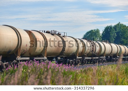 Set of train tanks with oil and fuel transport by rail - countryside view - stock photo