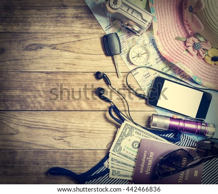 Set of travel accessory for female with mobile phone on wooden vintage background