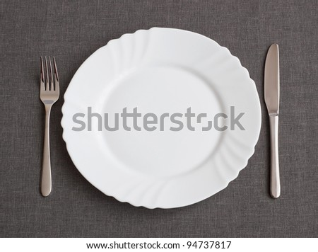 Set of utensil for dinner: plate, fork and knife - stock photo