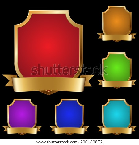 Set of varicolored decorative golden shields with banner isolated on black background. - stock photo