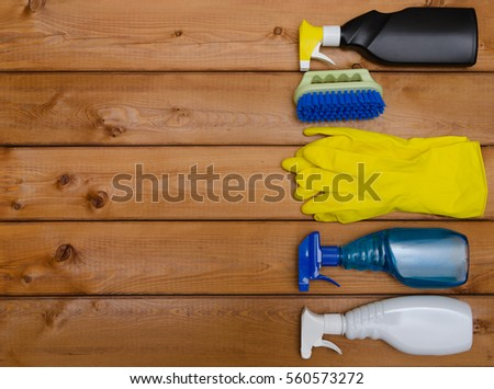 Set of variety cleaning supplies on wooden table, top view