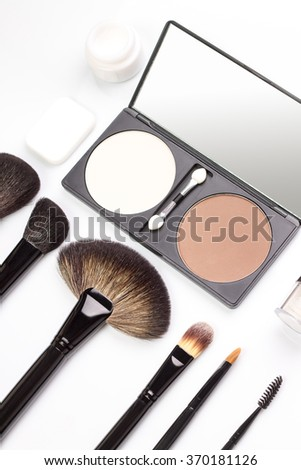 Set of various makeup brushes with eyeshadows and rouge or powder. Overhead view of cosmetics stuff - stock photo