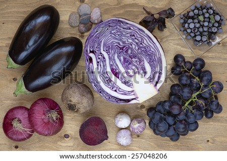 Set of vegetables and berries on aged wooden background: onion, eggplant, cabbage, beetroot, garlic, basil, grape, black currant.  - stock photo