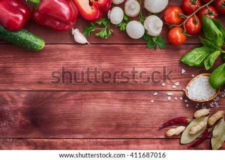 Set of vegetables, herbs and spices for salad. Wooden background. Top view