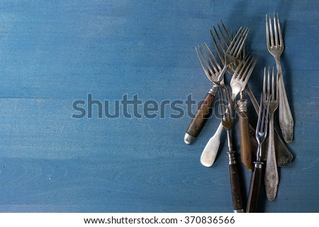 Set of vintage forks over blue wooden surface. Top view - stock photo