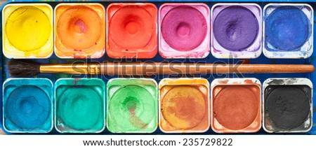Set of watercolor paints and paintbrush. Top view. - stock photo