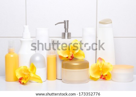set of white cosmetic bottles and hygiene supplies with orange flowers over tiled wall in bathroom - stock photo