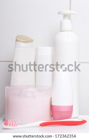 set of white cosmetic bottles over tiled wall in bathroom