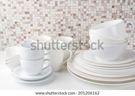 Set of white dishes on white kitchen table - stock photo
