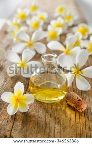 Set of white frangipani and massage oil on old wood
