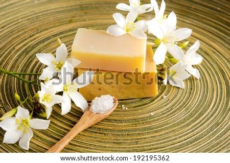 Set of white frangipani and salt in spoon and soap on wooden plate