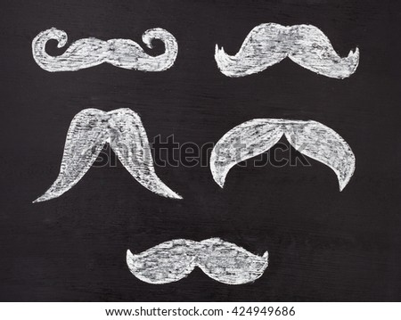 Set of white moustaches hand drawn with chalk on blackboard. Movember men's health awareness concept. - stock photo