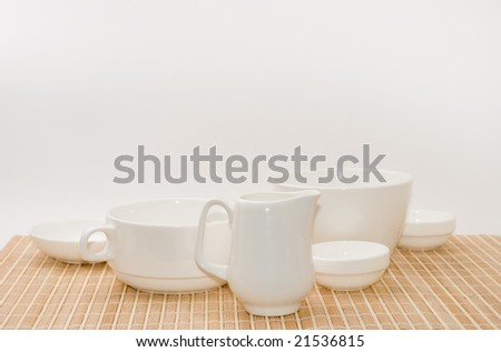 Set of white utensils on a bamboo support - stock photo
