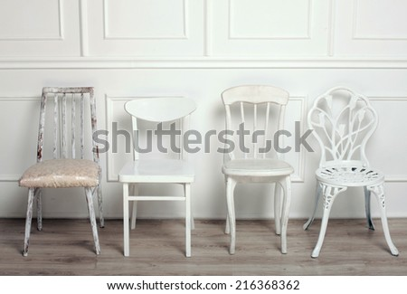 Set of white wooden vintage chairs standing in front of a white wooden wall on light parquet floor.  - stock photo
