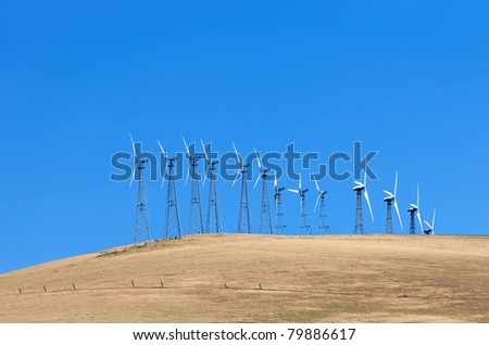 Set of windmills on the cornfield with blue sky in California - stock photo