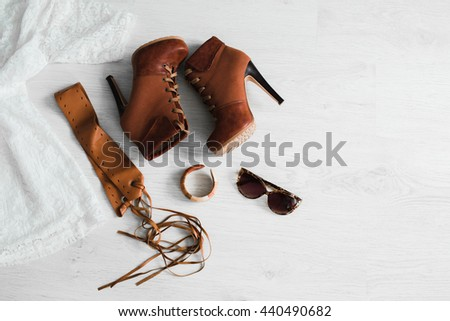 Set of women clothes and shoes. Bright dress, brown boots, belt, accessories. Boho - stock photo