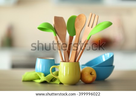 Set of wooden kitchen utensils in green cup with napkin and dishes on the table - stock photo