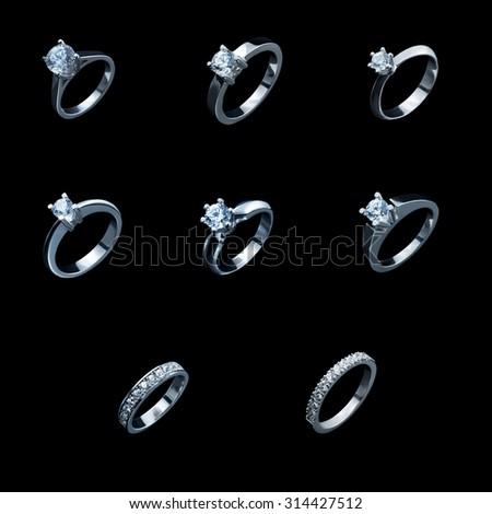 set silver or white gold diamond rings on black background - stock photo