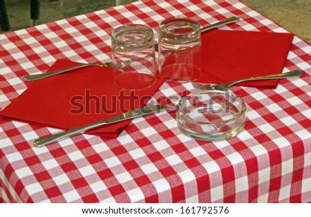 set table with tablecloth red and white checked by an Italian trattoria