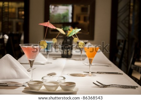 set up of a dining table with different juices in wine glasses - stock photo