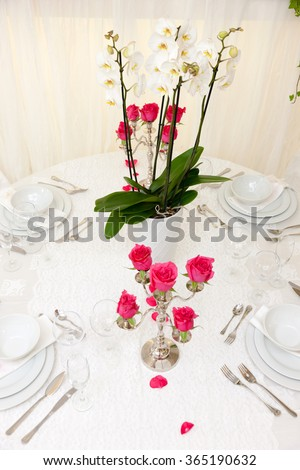 set up of a wedding table decorated with flowers