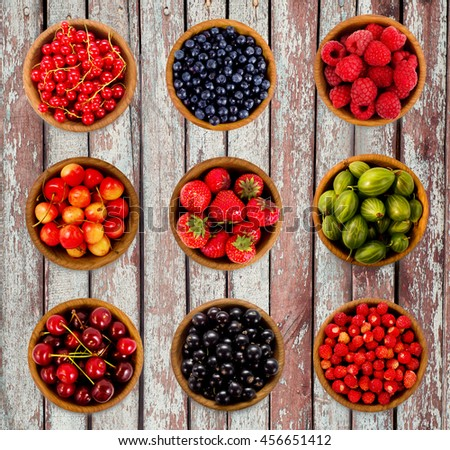 Set various berries. Strawberries, currant, cherry, raspberries, gooseberries and bilberry. Collage of different fruits and berries isolated on a wooden background - stock photo