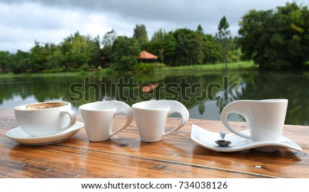 set white cup coffee on wood, blurred green tree  and lake background.
