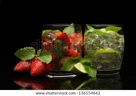 set with mojito lime and strawberry cocktails on black background - stock photo