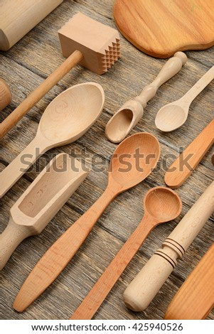 Set wooden kitchen utensils on wooden table. Spoon, fork, rolling pin, hammer kitchen, kitchen spatula. Top view. - stock photo