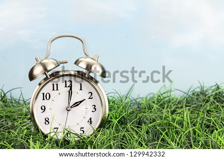 Set your clocks back with this clock in grass against a bright sky. Daylight saving time concept. - stock photo