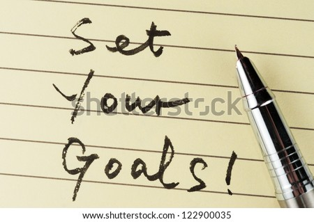Set your goals words written on lined paper with a pen on it