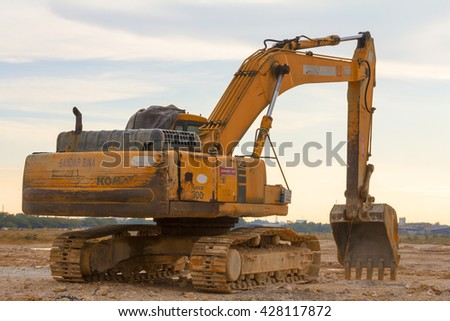 Setia Alam, Malaysia 29 May 2016, Yellow excavator on a construction site against sunset.