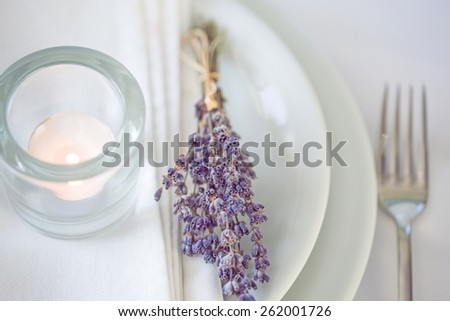 Setting. Dining table setting at Provence style, with candles, lavender, vintage crockery and cutlery, closeup. - stock photo
