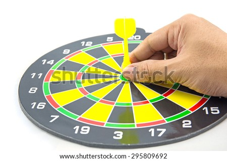 Setting goal or accurate planning, hand going to take dart into the center of dartboard - stock photo