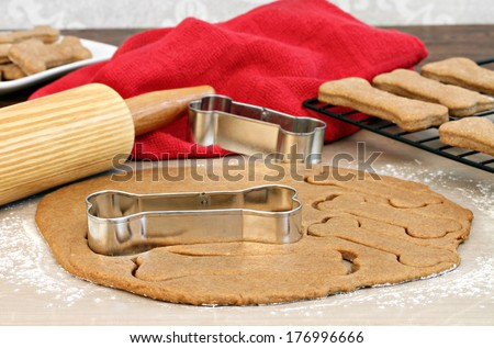 Setting of a rolling pin and dog bone cookies cutters. Selective focus on cookie cutter and dough. - stock photo