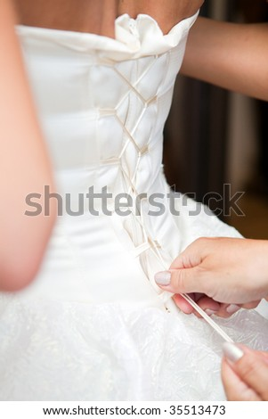 Setting of laces on a corset of a dress of the bride - stock photo