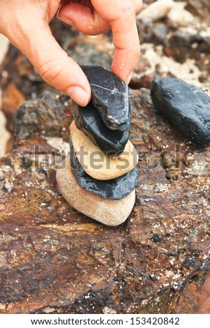 Setting stone stack on the brown rock - stock photo
